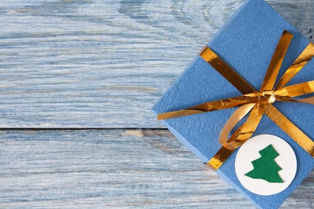 Caja de regalo azul con cinta dorada sobre madera azul para navidad y año nuevo, cumpleaños o san valentín