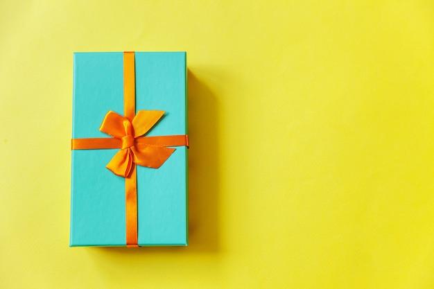 Caja de regalo azul de diseño simplemente minimalista aislada sobre fondo de colores amarillo
