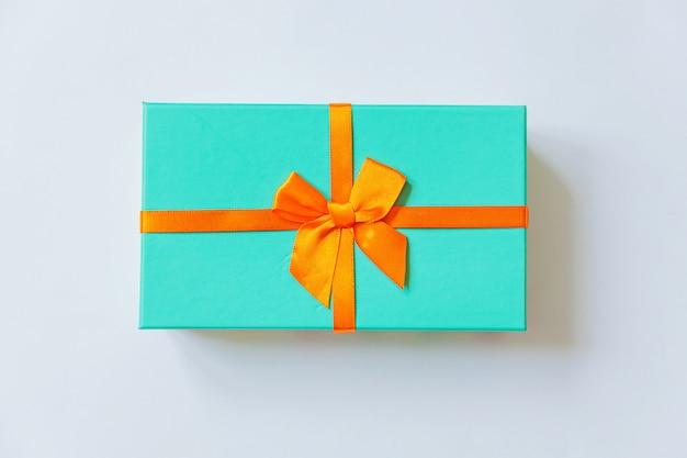 Caja de regalo azul de diseño simplemente minimalista con cinta naranja aislada sobre fondo blanco