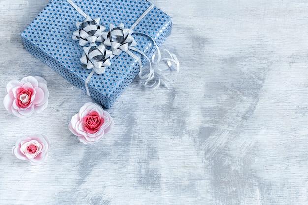 Caja de regalo azul en madera clara. san valentín, vacaciones y regalos.