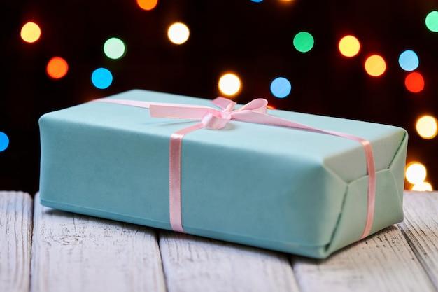 Una caja de regalo azul de navidad o año nuevo con cinta rosa sobre superficie de madera contra luces de colores