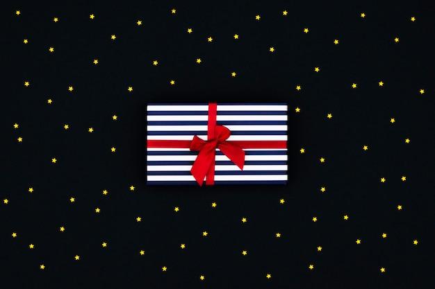 Caja de regalo azul a rayas con un lazo de raso rojo sobre fondo negro con muchas estrellas pequeñas.