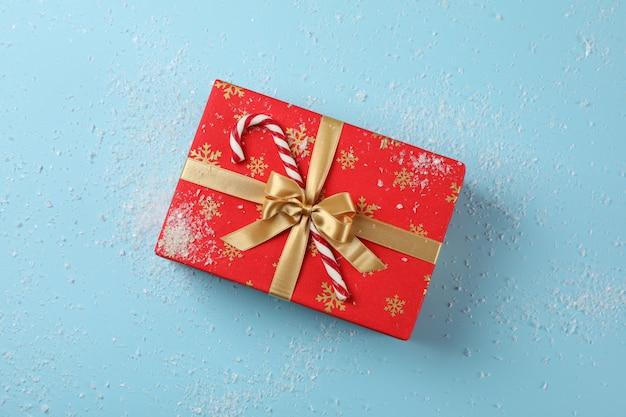 Caja de regalo, bastón de caramelo y nieve sobre fondo azul, vista superior