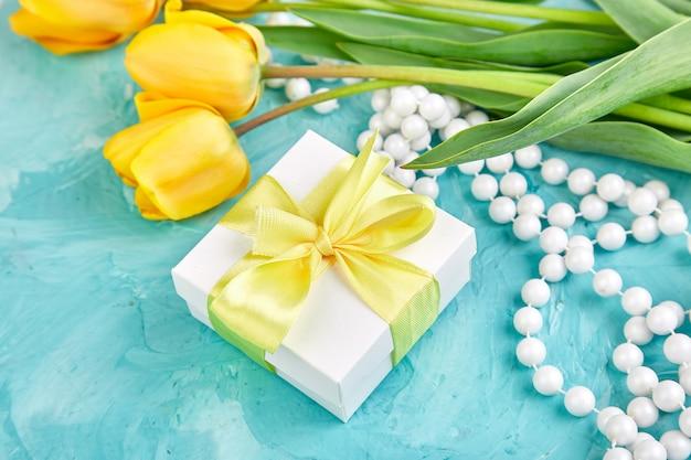 Caja de regalo blanca con cinta amarilla cerca de tulipán amarillo