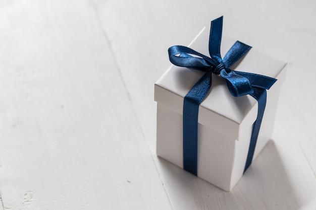 Una caja de regalo blanca con cinta de raso azul sobre madera blanca