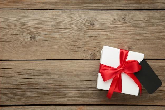 Caja de regalo blanca con cinta roja con etiqueta de venta aislada en madera gris