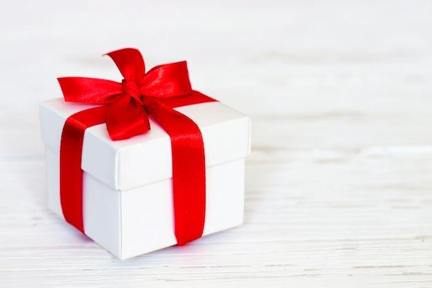Caja de regalo blanca con una cinta roja sobre un fondo blanco de madera, copia. concepto de tarjeta de felicitación concepto de regalo