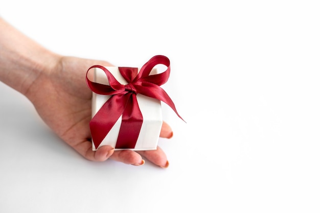Caja de regalo blanca con lazo rojo se encuentra en una mano de mujer sobre fondo blanco.