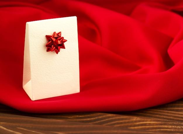 Caja de regalo blanca con lazo rojo sobre una hermosa tela escarlata