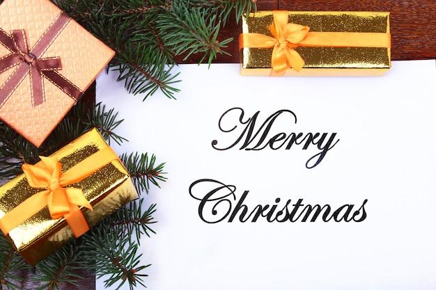 Caja de regalo, bolas de colores y árbol de navidad en un escritorio de madera con letra para copiar el espacio.