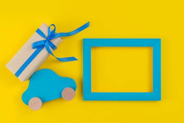 Caja de regalo con carro de juguete y marco sobre mesa.