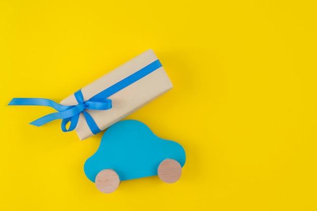 Caja de regalo con carro de juguete en mesa amarilla.