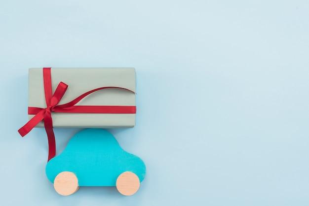 Caja de regalo con carro de juguete en mesa.