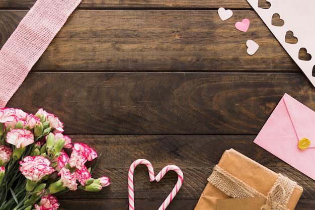 Caja de regalo cerca de flores, sobre y bastones de caramelo.