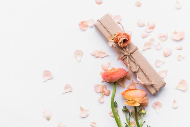 Caja de regalo cerca de flores sobre pétalos.