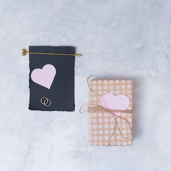 Caja de regalo cerca de papel negro y símbolos de corazón.