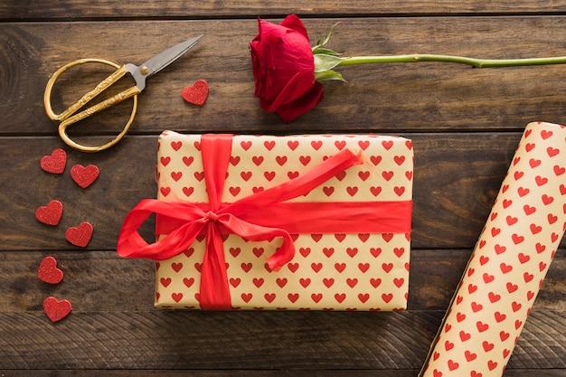 Caja de regalo cerca de rollo de papel cariño, tijeras y flor.