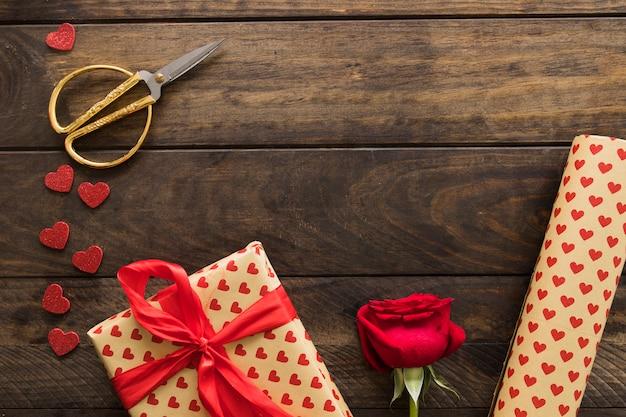Caja de regalo cerca de rollo de papel cariño, tijeras y floración.