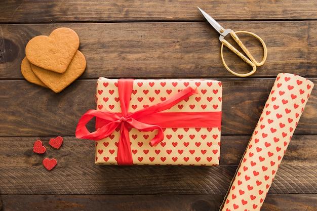 Caja de regalo cerca de rollo de papel cariño, tijeras y galletas.