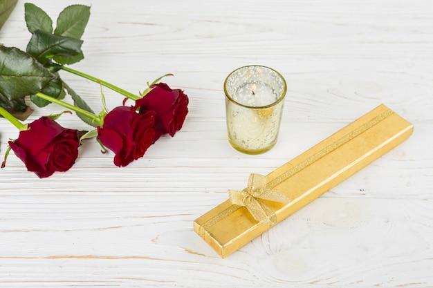 Caja de regalo cerca de vela y flores.