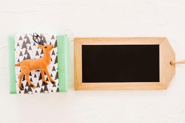 Caja de regalo cerca de venado de juguete y etiqueta