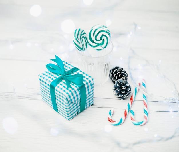 Caja de regalo cerca de vidrio con paletas, bastones de caramelo y luces de colores.