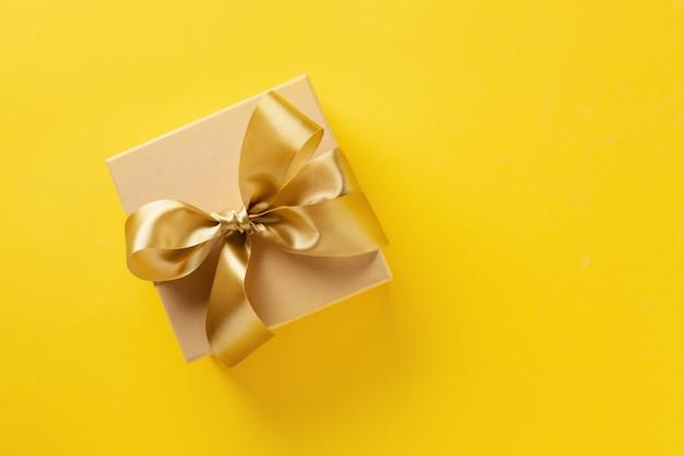 Caja de regalo con cinta dorada sobre fondo brillante