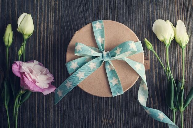 Caja de regalo con cinta de estrella en mesa rústica oscura