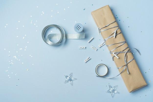 Caja de regalo con cinta en mesa azul.