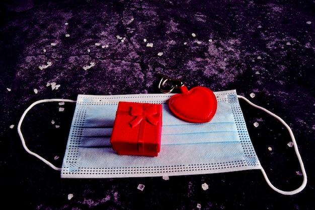 Caja de regalo con cinta roja y corazón en una máscara médica sobre un hormigón negro