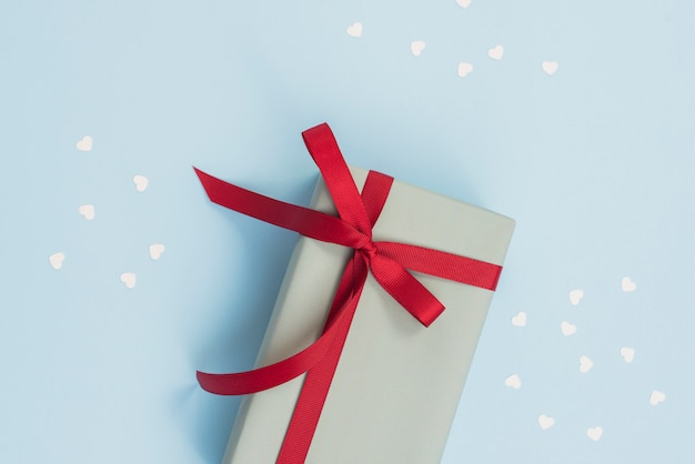 Caja de regalo con cinta roja en mesa