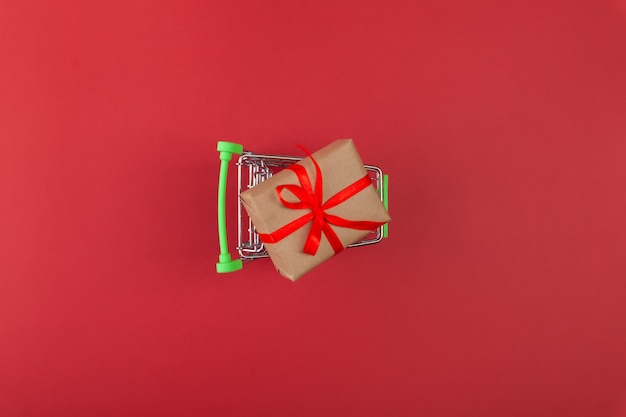 Caja de regalo con cinta roja en mini carrito de supermercado