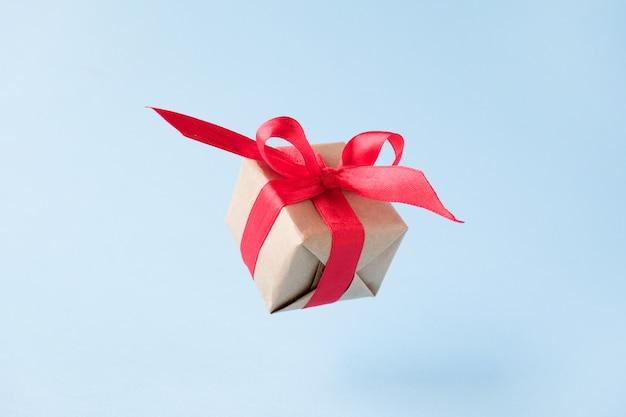 Caja de regalo con cinta roja sobre azul.