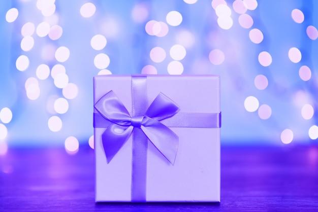 Caja de regalo con cinta roja sobre fondo de color neón de moda.