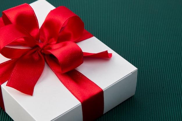 Caja de regalo con cinta sobre papel verde.