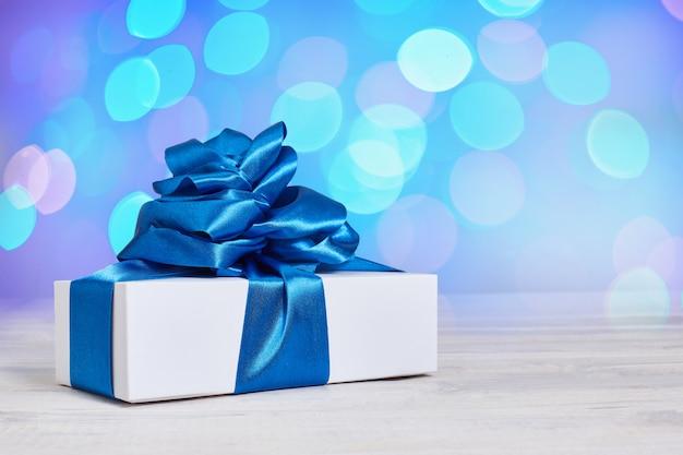 Caja de regalo con un clásico lazo azul sobre un fondo con fondo desenfocado bokeh