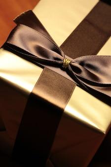 Caja regalo de color dorado con cinta marrón