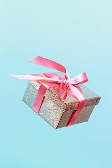 Caja de regalo de color dorado con cinta rosa sobre fondo azul.
