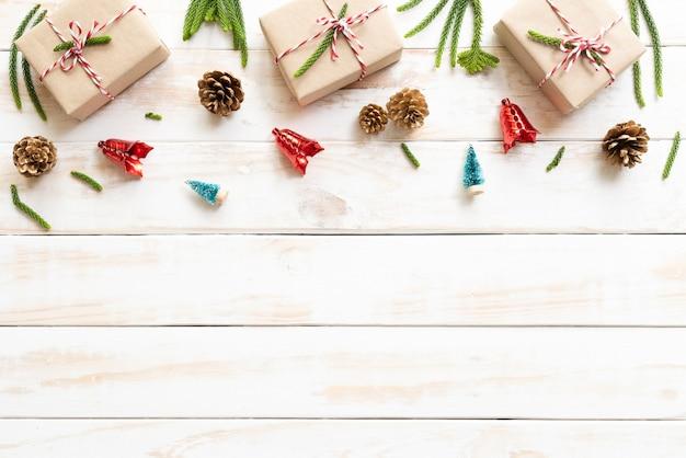 Caja de regalo, conos de pino, estrella roja y campana sobre un fondo blanco de madera. ddecoratio de navidad