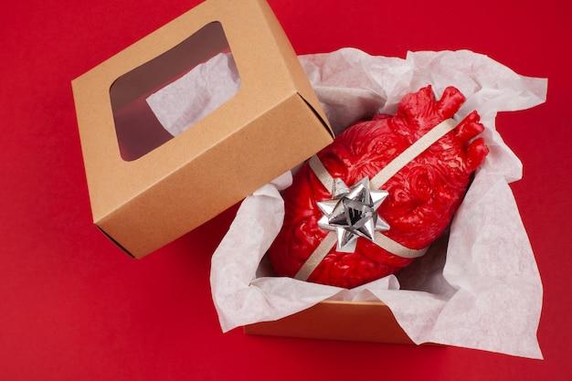 Caja de regalo con el corazón realista dentro como un regalo.