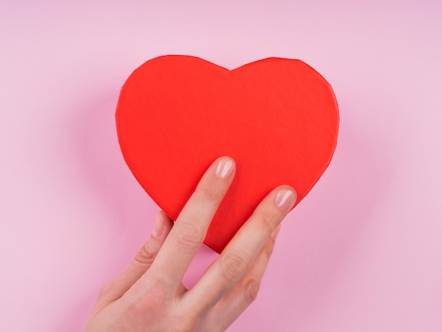 Caja de regalo de corazón rojo sobre fondo rosa