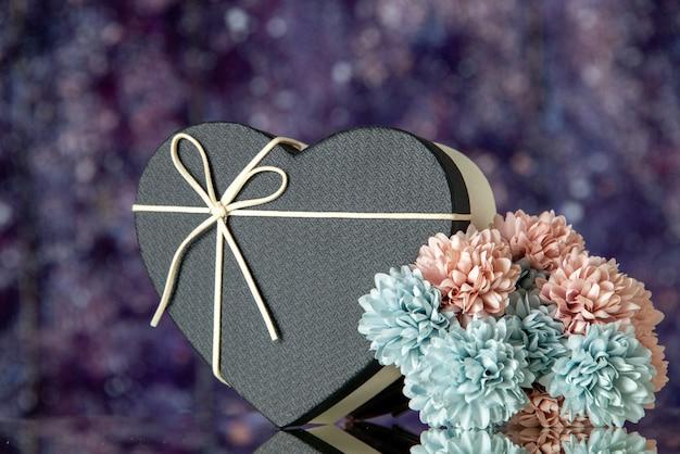 Caja de regalo de corazón vista frontal con flores de colores de cubierta negra sobre fondo borroso púrpura