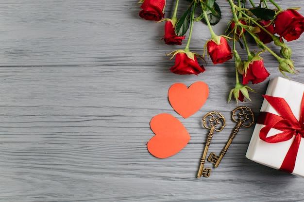Caja de regalo con corazones de papel en mesa gris.