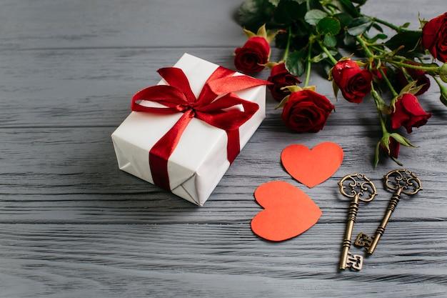 Caja de regalo con corazones de papel en mesa