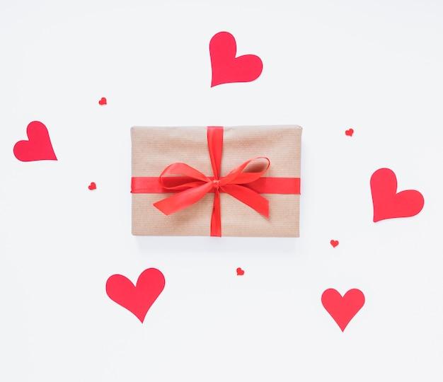 Caja de regalo con corazones rojos en mesa de luz