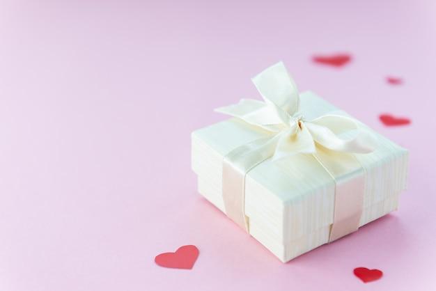 Caja de regalo con corazones sobre un fondo rosa.
