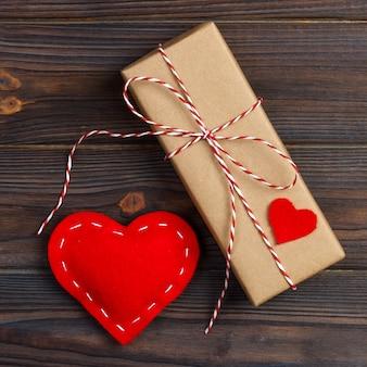 Caja de regalo con corazones de tela en mesa de madera negra.
