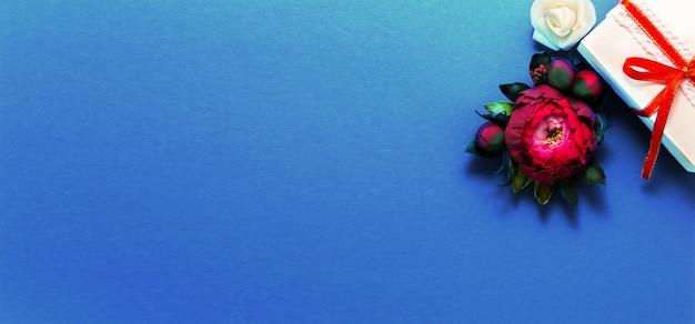 Caja de regalo decoración actual flatlay. regalo cinta roja rosa flores blancas vista superior