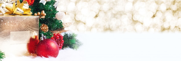 Caja de regalo y decoración de bolas debajo del árbol de navidad en abeto blanco con fondo bokeh