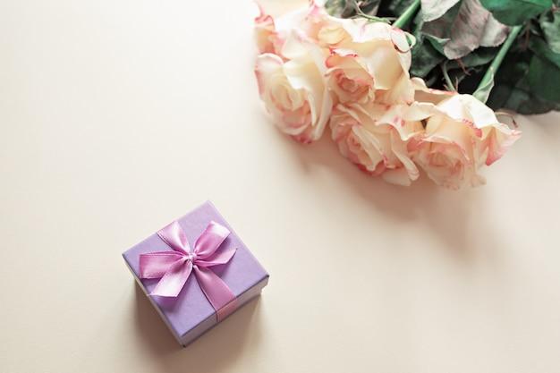 Caja de regalo con decoraciones y rosas sobre la mesa.